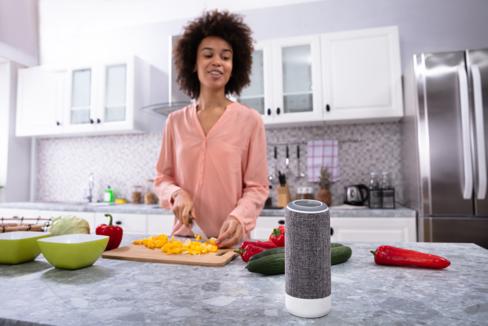 Woman in Kitchen Talking to Smart Speaker