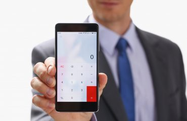 Businessman with Smartphone Calculator